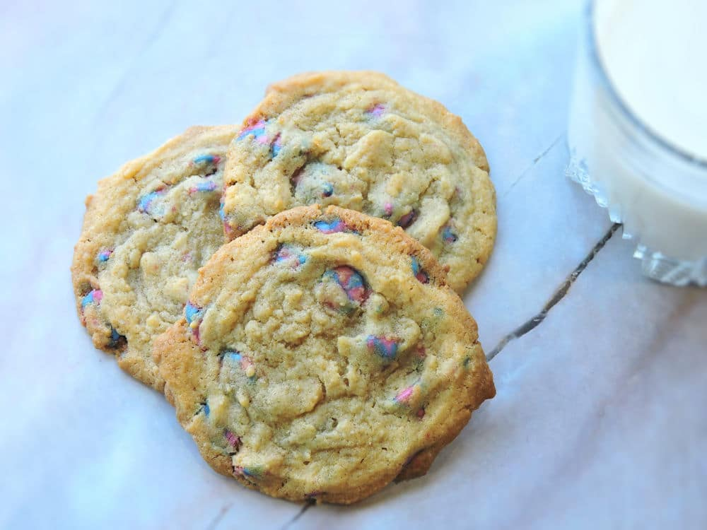 Unicorn chip cookies on a marble counter with a glass of milk