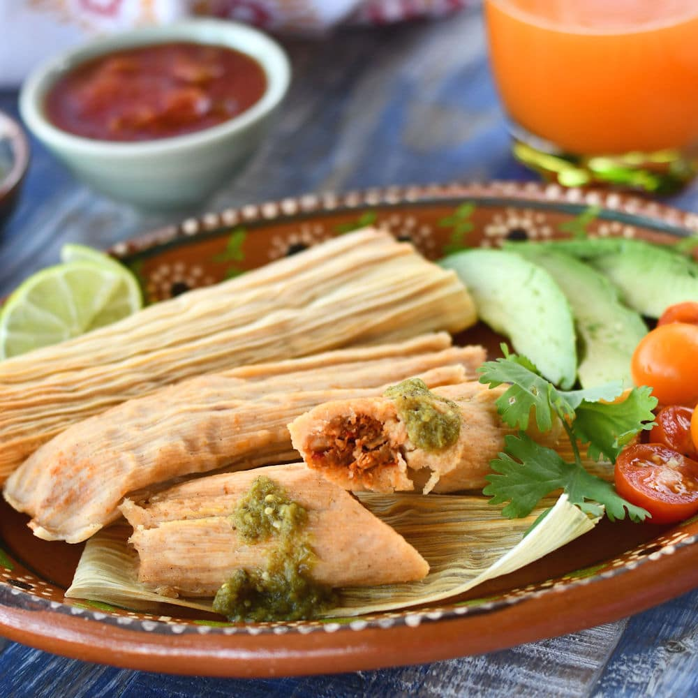 24Bite: traditional pork tamales served with avocado, chopped tomato salad and lime