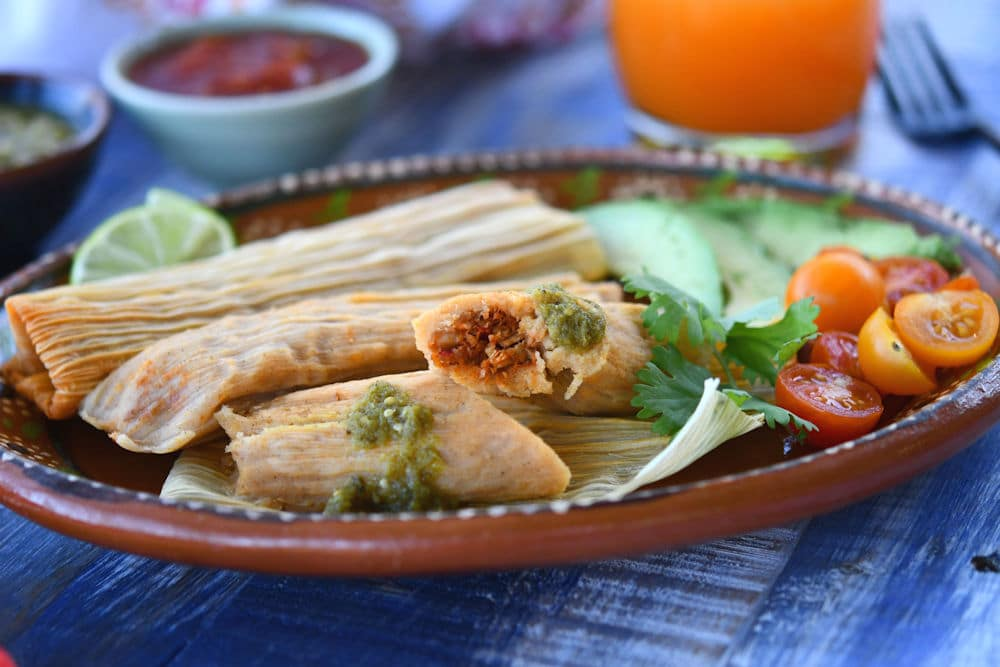 24Bite: Plate of pork tamales served with tomato salad and lime slices