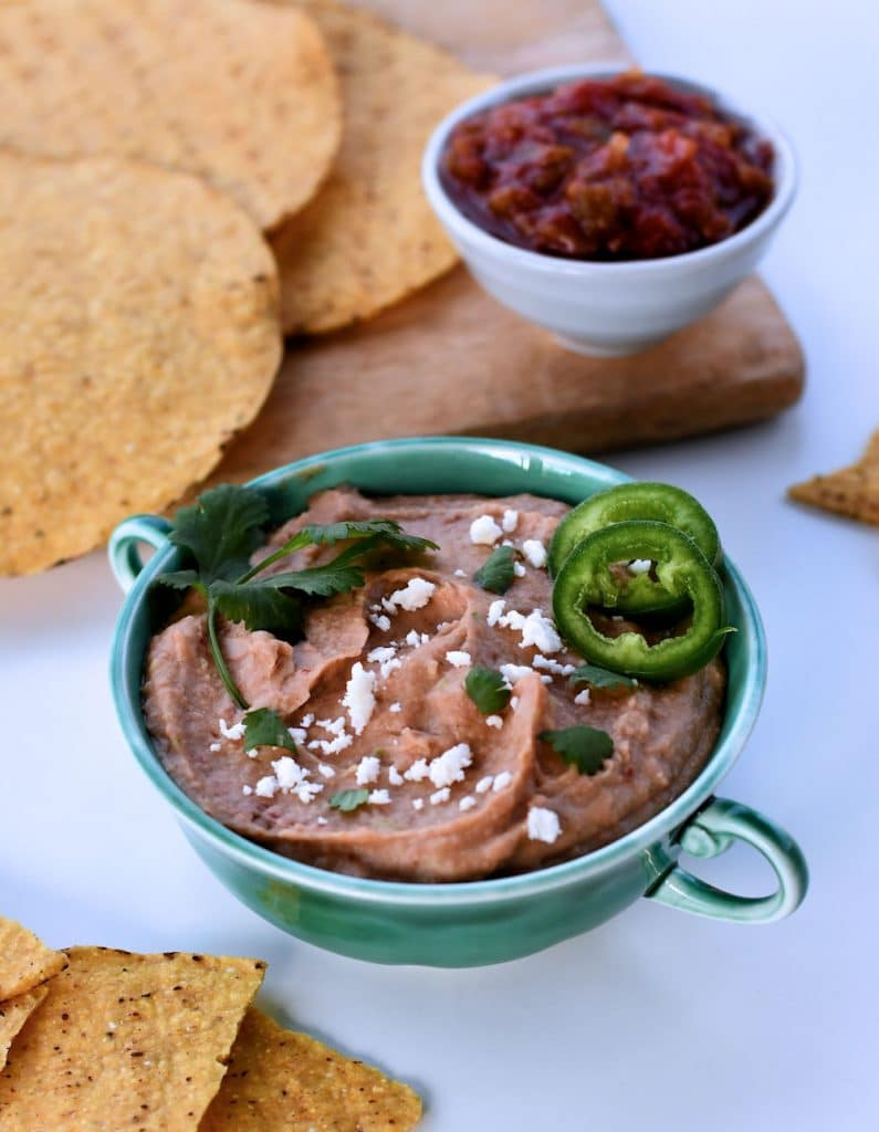24Bite: Small two-handled bowl with instant pot vegan bean dip shown with tostadas and salsa