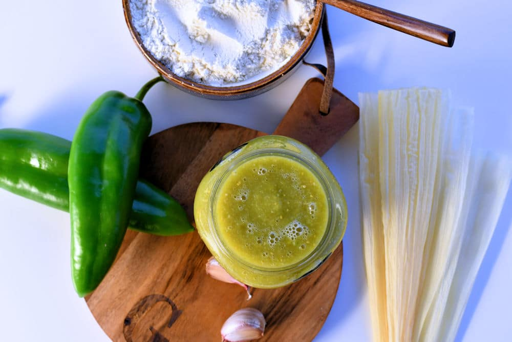 green tamale sauce in a jar shown on a counter with anaheim chiles and corn husks.