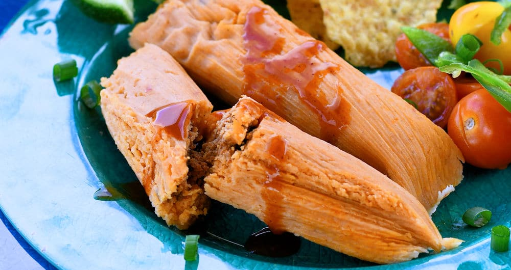 Chorizo tamales on a plate with a tomato salad