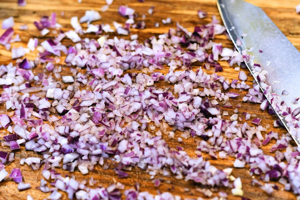 finely chopped red onion on cutting board