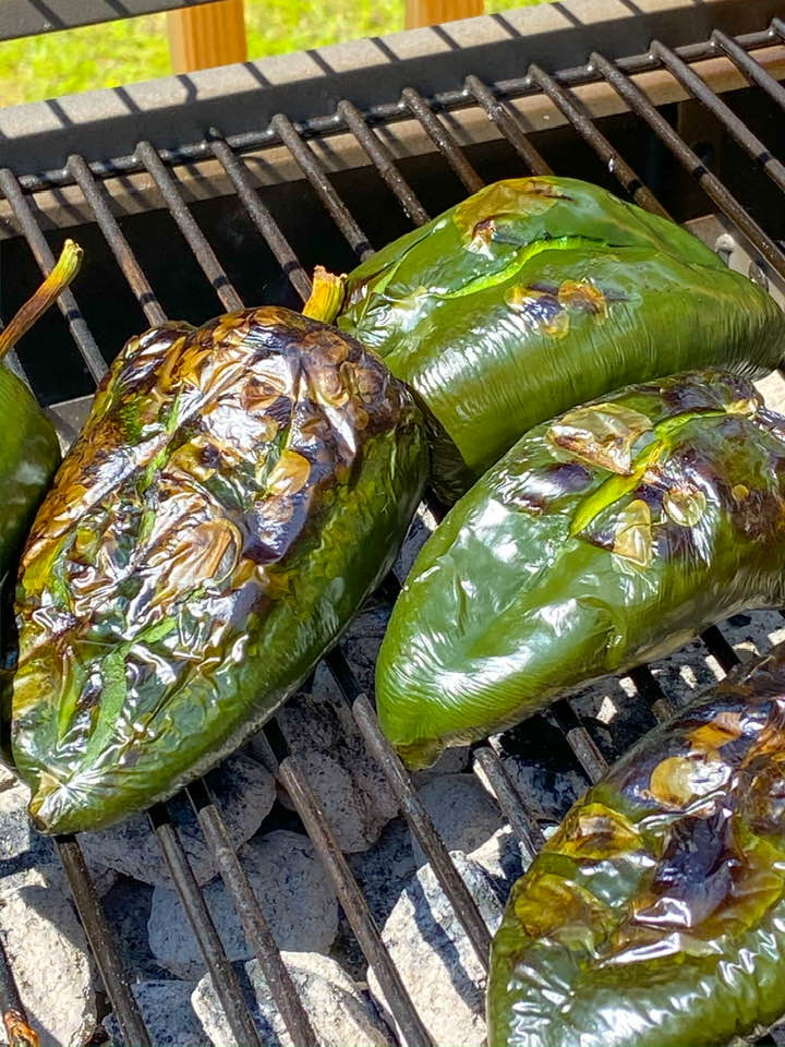 charred poblano peppers shown on an outdoor grill