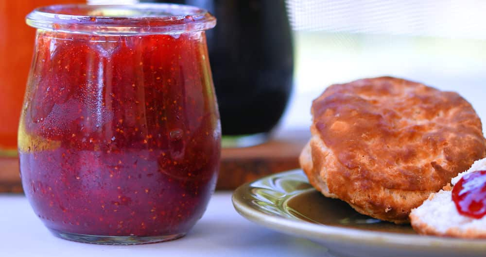 Jar of homemade strawberry jelly and biscuits