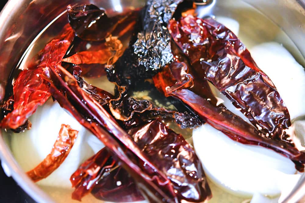 The dried chiles, onion and garlic are steamed in water to reconstitute them.