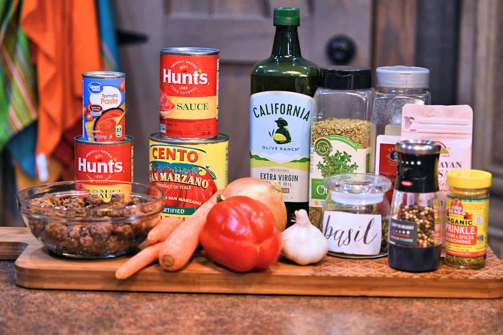 ingredients for homemade spaghetti sauce displayed on a cutting board