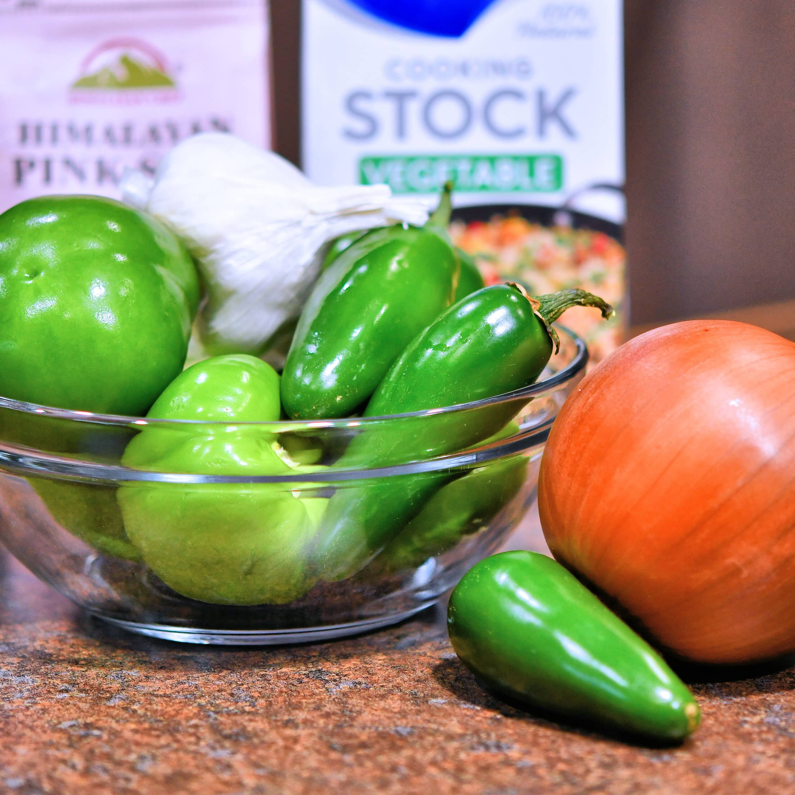 Glass bowl with tomatillos, jalapenos, garlic and onion.