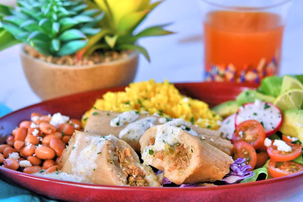 chicken tamales shown on a red stoneware plate with a tomato salad and red beans.