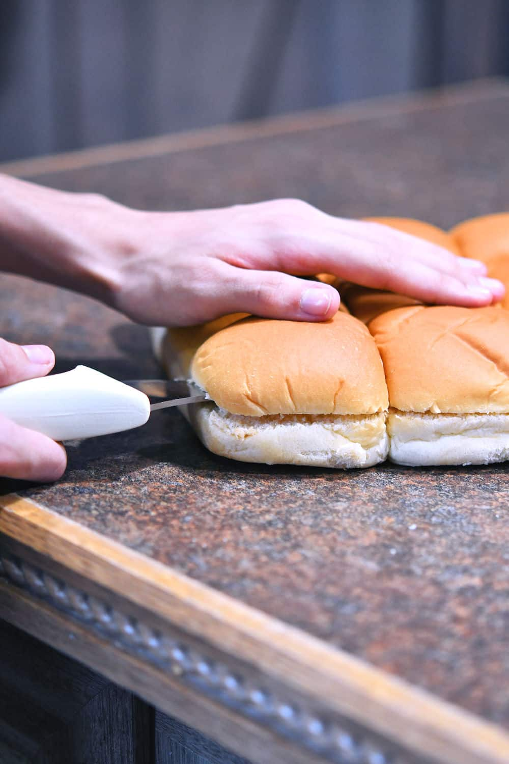 dinner rolls on a counter being cut through the horizontal center with a long serrated bread knife