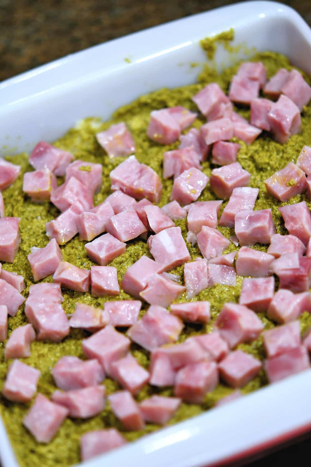cubed ham sprinkled over the top of the pesto for the sliders