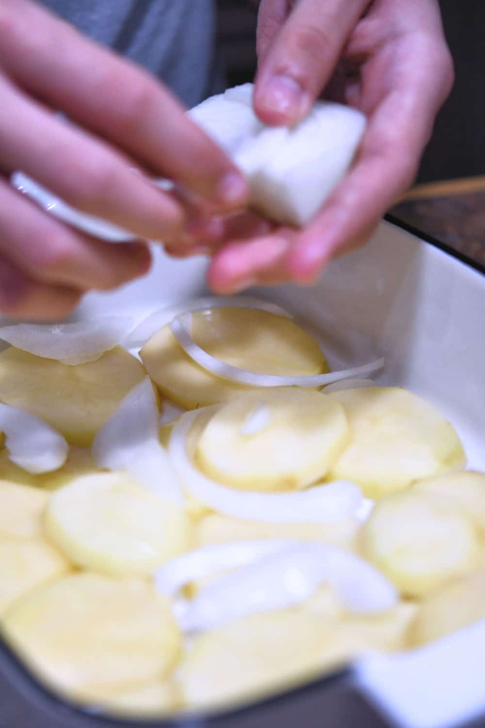 layering the sliced potatoes in the baking pan with a little bit of onion slivers