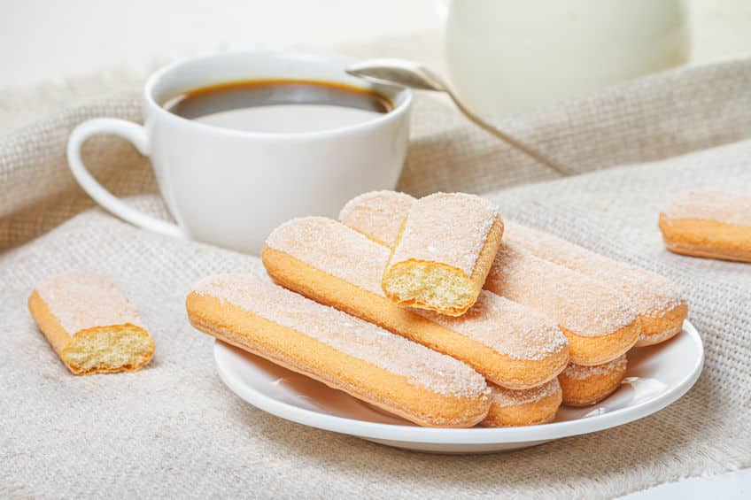 """stack of ladyfinger biscuits on a white plate with a cup of coffee to the side. Copyright: <a href=""""https://www.123rf.com/profile_rustamank"""">rustamank / 123RF Stock Photo</a>"""