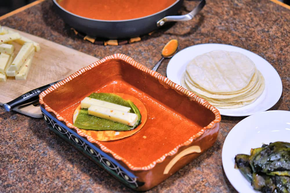 cheese, container of sauce, tortillas and peeled green chiles shown on a counter for assembling cheese enchiladas