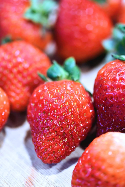 closeup of fresh raw strawberries on a wooden cutting board