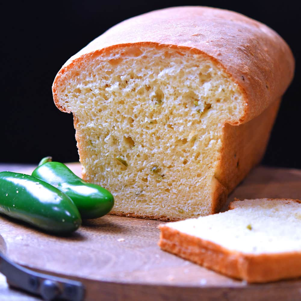 loaf of jalapeno cheese bread on a cutting board, with a slice to the side