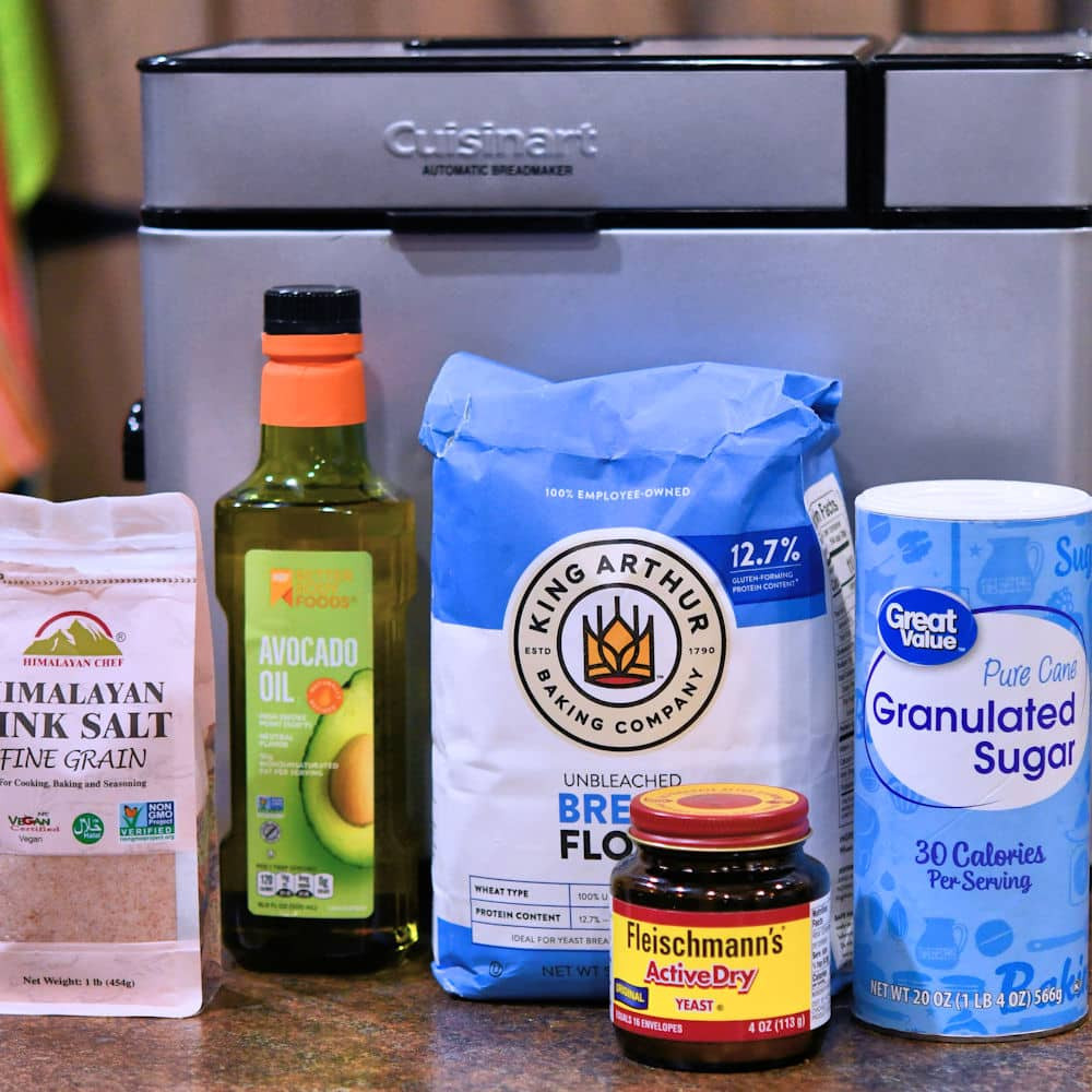 ingredients for pizza dough recipe displayed on a countertop with a cuisinart bread machine
