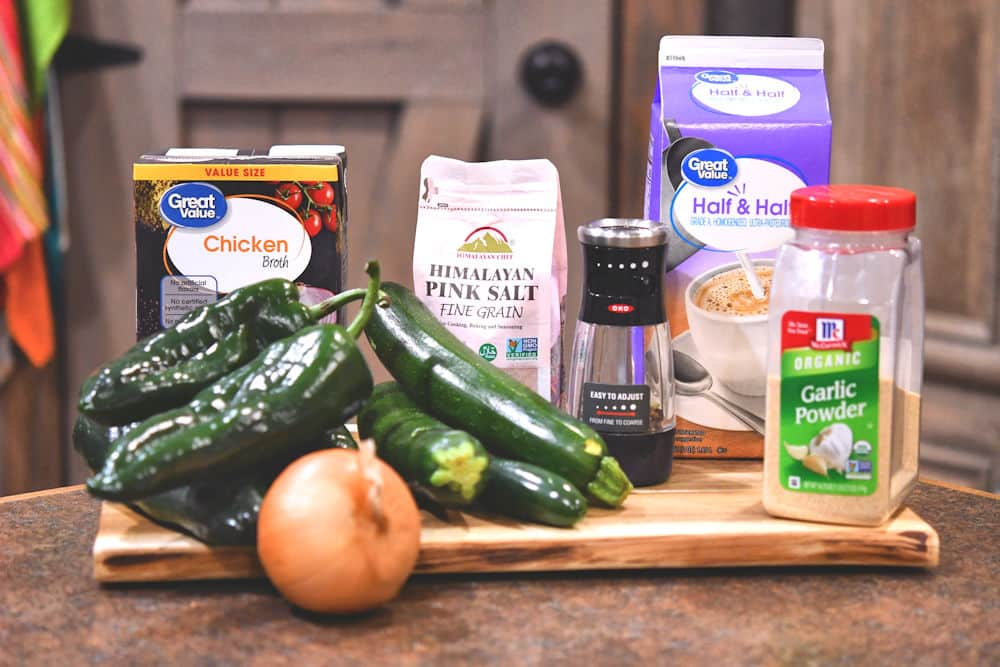 zucchini and spicy green chiles with other ingredients for soup on a cutting board