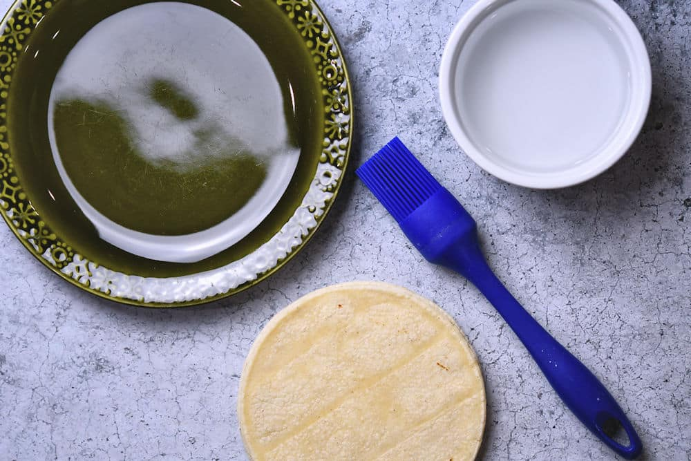 plate, bowl of water and pastry brush on a counterop to soften corn tortillas