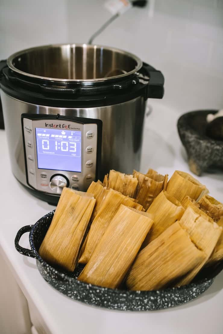 Pork green chile tamales on a counter beside an Instant Pot