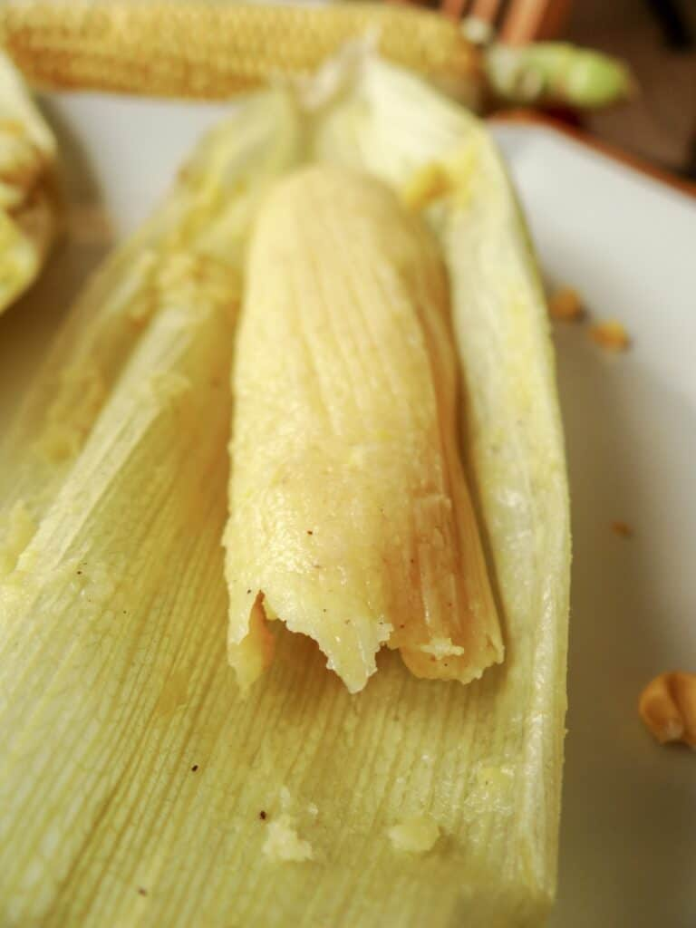 Open sweet corn tamales, sereved on a white plate.