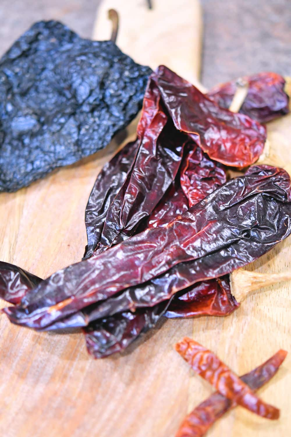 ancho, Anaheim and Arbol chiles on a wooden cutting board