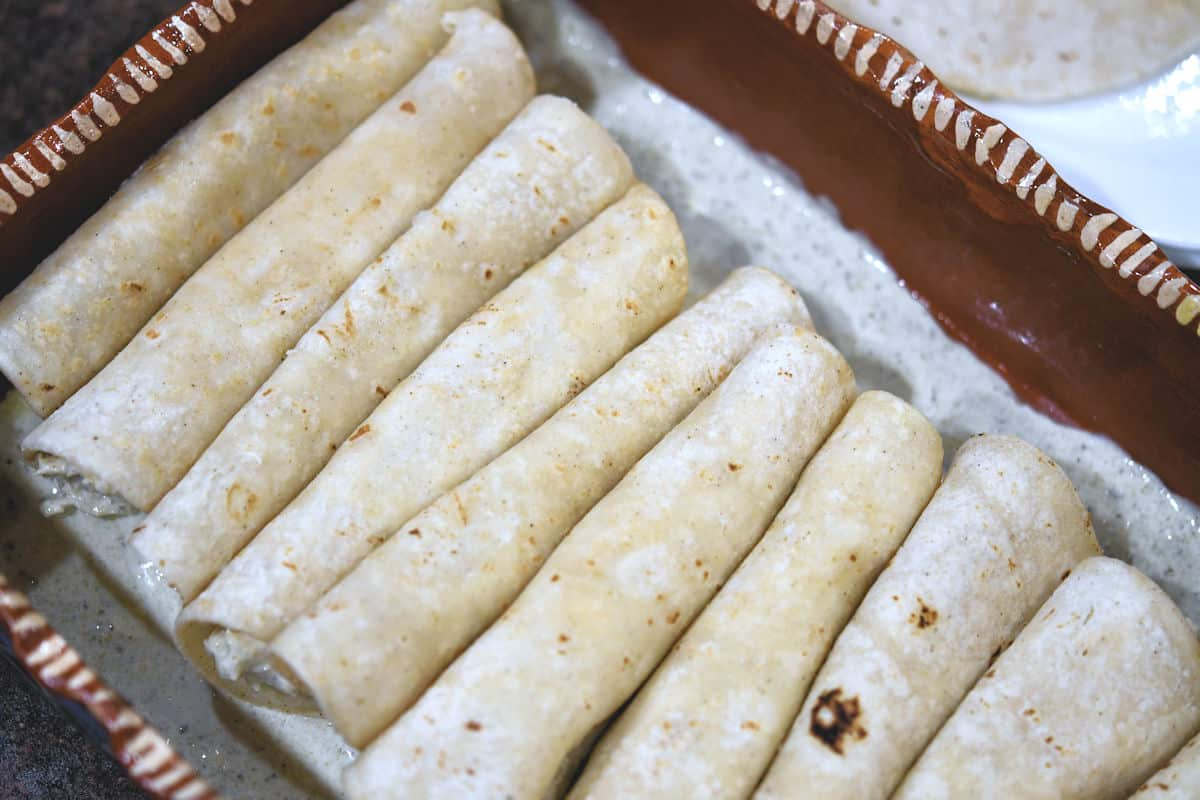 Baking pan with rolled tortillas, ready for topping and cheese