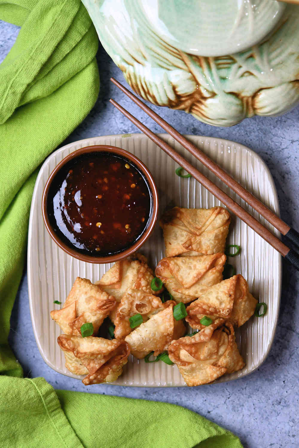 fried shrimp rangoon on a plate with a bowl of sweet chili sauce and chopsticks