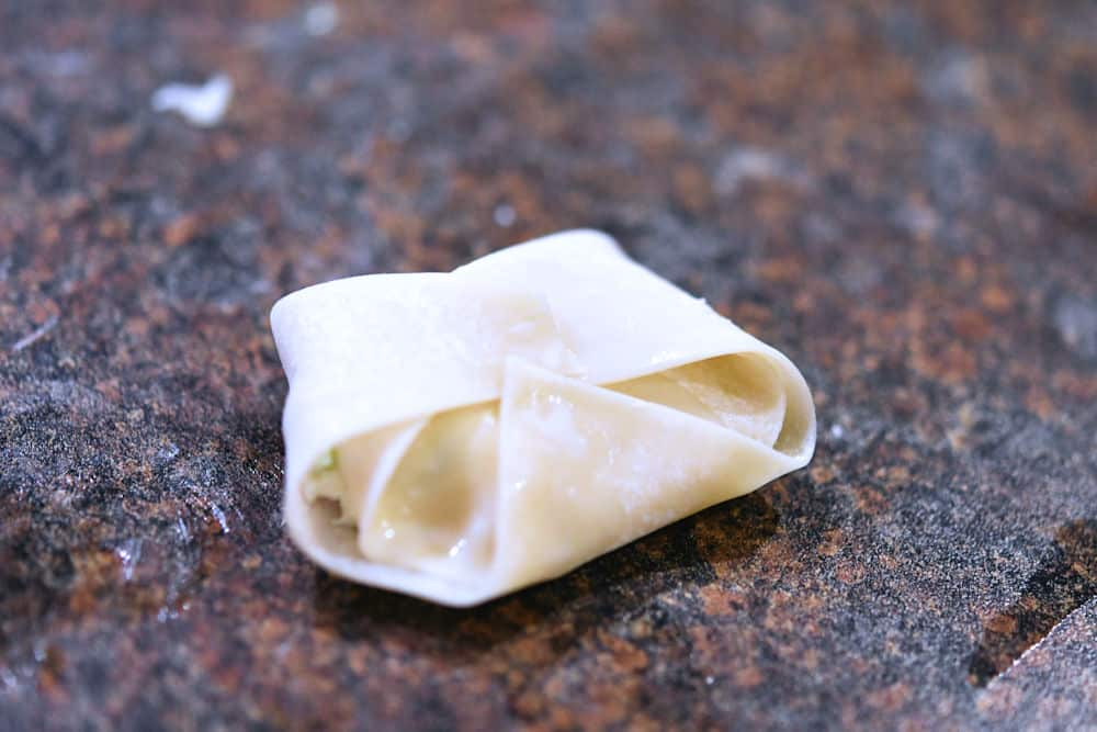 a wrapped rangoon ready to be fried or baked