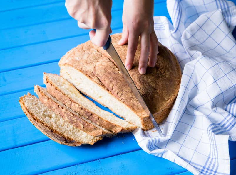 closeup of large round loaf of bread with slicing being cut © to 123rf.com