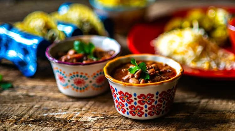 slow cooked pinto charro beans in little cups on a wooden block table