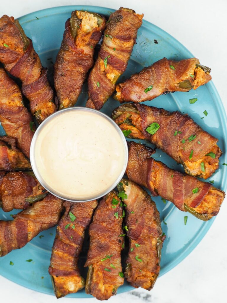 blue plate of bacon wrapped jalapeno poppers