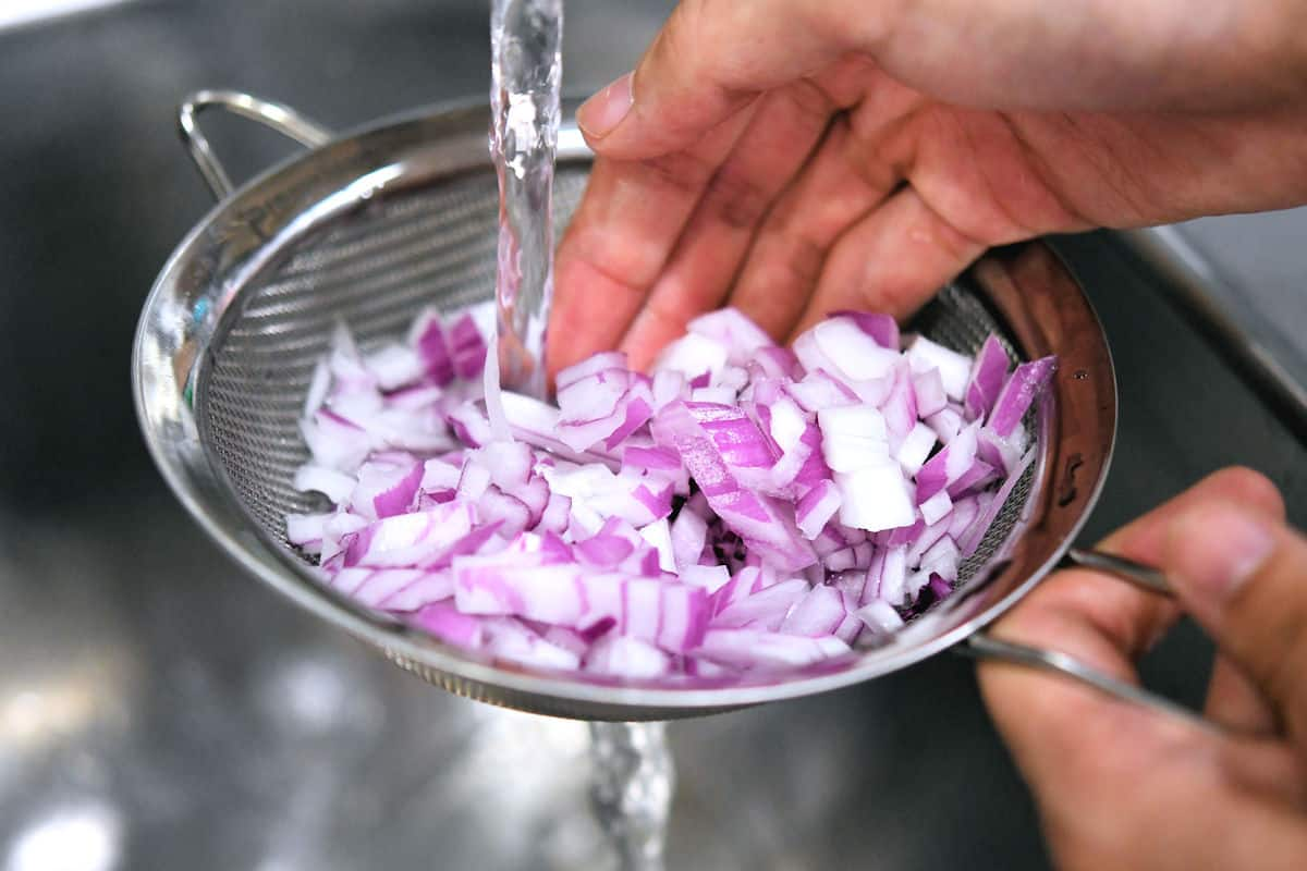 chopped onion in a mesh strainer, running cool water over them to deflame them