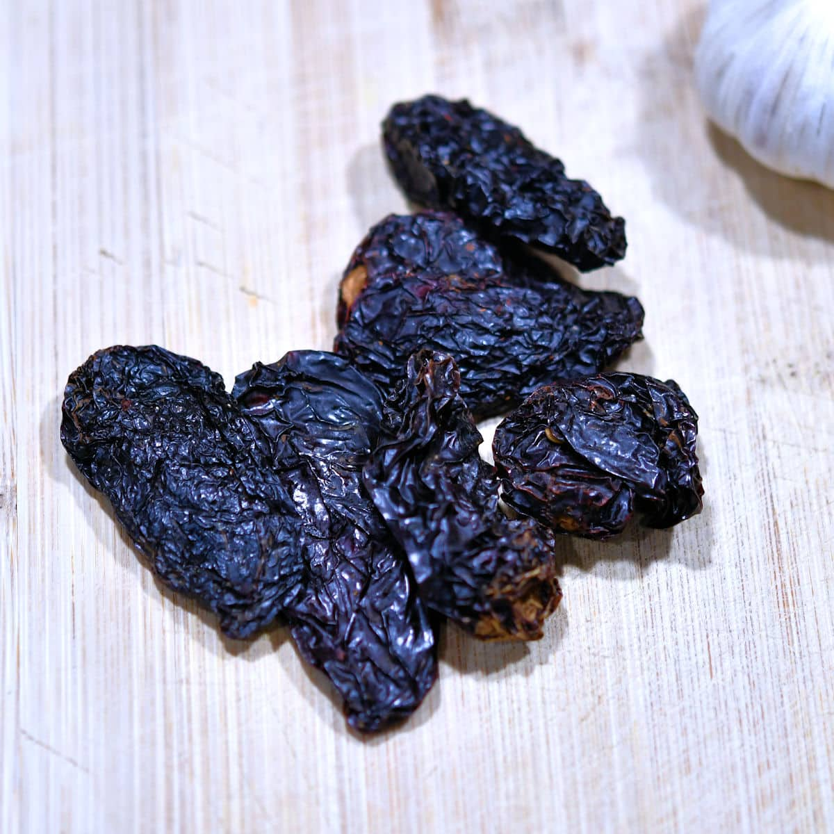 handful of dried chipotle peppers on a cutting board