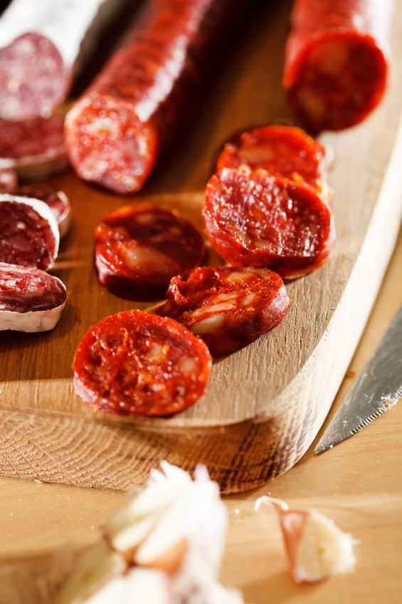 Sliced Spanish chorizo sausage on a cutting board © Maksim Shebeko via 123rf