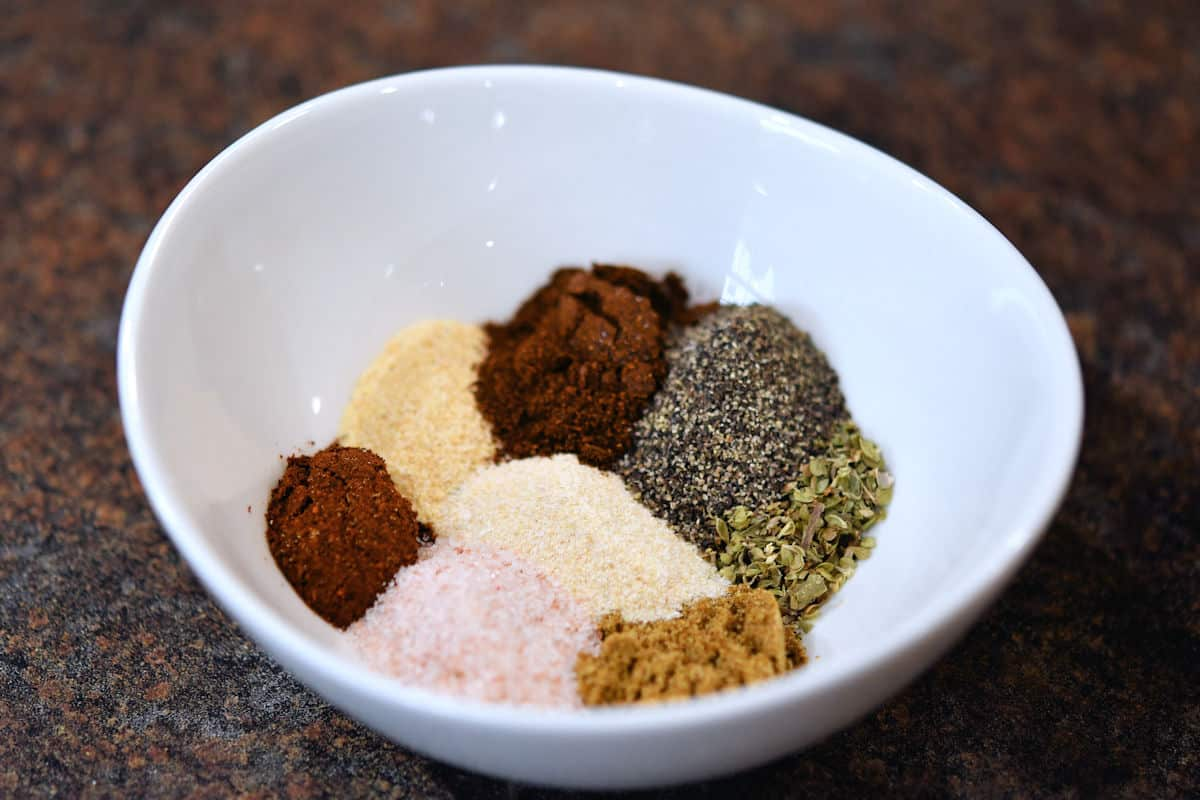a little white bowl with a variety of fajita spices