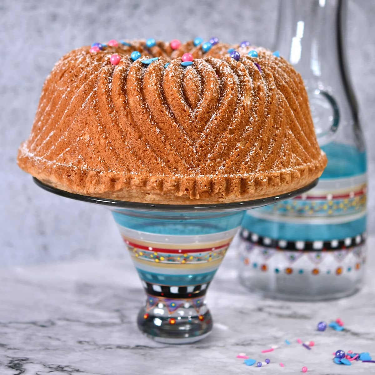 Uncut pound cake on a pedestal, decorated with powdered sugar and candy decorations