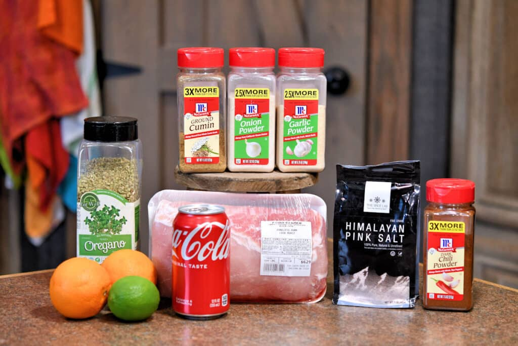 ingredients for pork carnitas from recipe card below, displayed on a countertop