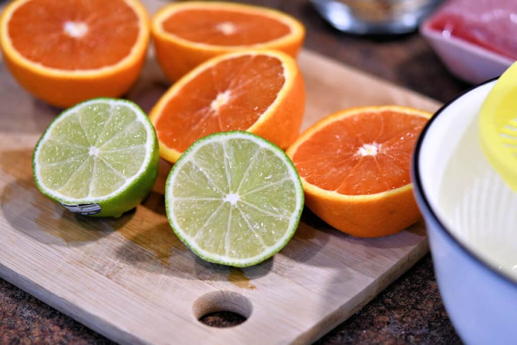 oranges and limes cut in half on a cutting board